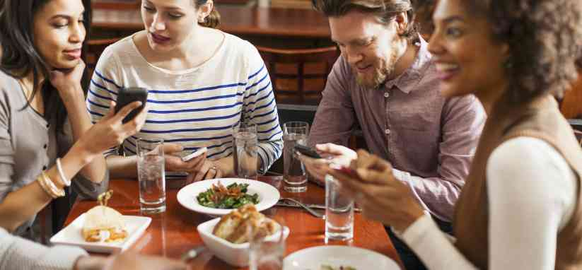 Friends at restaurant using cell phones