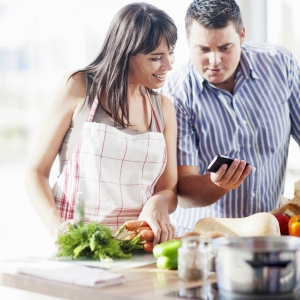 A couple cooking together in the kitchen and looking at a smartphone
